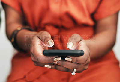 Buy stock photo Cropped shot of an unrecongnizable businesswoman sitting alone in the office and texting on her cellphone