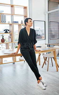Buy stock photo Full length shot of an attractive young businesswoman leaning on her desk and looking contemplative in her office