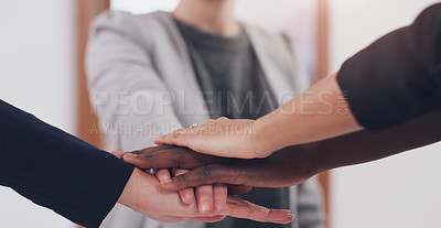 Buy stock photo Cropped shot of a group of unrecognizable businesspeople joining their hands together in a huddle in a modern office