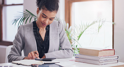 Buy stock photo Cropped shot of an attractive young businesswoman using a calculator and a notebook while  working on her finances in her office