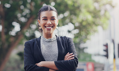 Buy stock photo Cropped portrait of an attractive young businesswoman smiling while standing with her arms crossed outdoors in the city