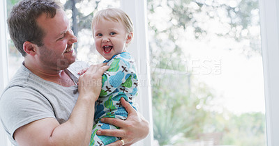 Buy stock photo Cropped shot of an affectionate young father smiling while holding his baby girl at home