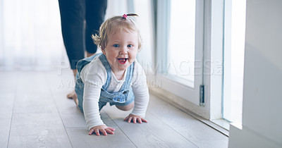 Buy stock photo Cropped shot of an adorable little baby girl crawling on the floor with her mother walking behind her at home