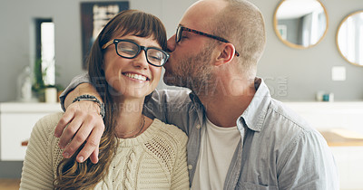 Buy stock photo Cropped shot of an affectionate young man kissing his wife while spending time with her indoors at home