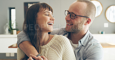 Buy stock photo Cropped shot of an affectionate young couple smiling at each other while spending time together indoors at home