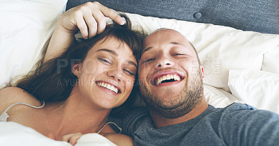 Buy stock photo High angle portrait of an affectionate young couple taking a selfie together while lying in their bed at home