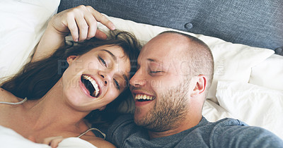 Buy stock photo High angle shot of an affectionate young couple taking a selfie together while lying in their bed at home