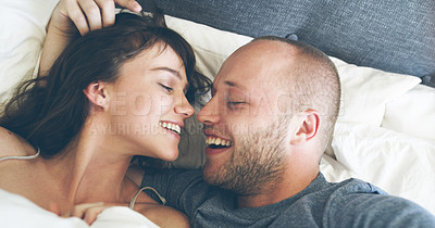 Buy stock photo High angle shot of an affectionate young couple kissing each other while taking a selfie in their bed at home