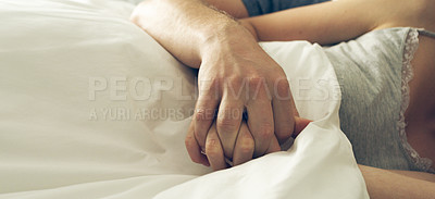 Buy stock photo Cropped shot of an unrecognizable couple holding hands while lying in bed at home