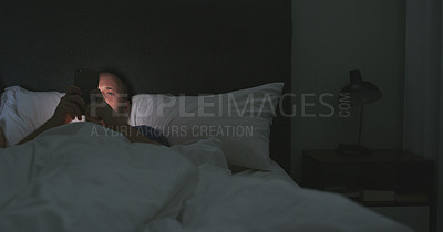 Buy stock photo Cropped shot of a handsome young man using his smartphone while lying bed at night