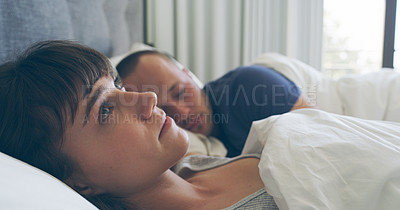 Buy stock photo Cropped shot of an attractive young woman looking thoughtful while lying in bed with her husband sleeping ext to her