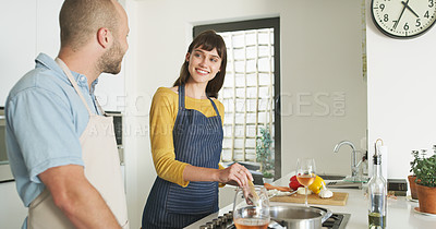 Buy stock photo Cropped shot of an affectionate young woman smiling at her husband while cooking in their kitchen at home