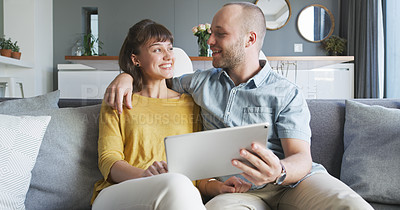 Buy stock photo Cropped shot of an affectionate young couple smiling at each other while using a digital tablet  in their living room at home
