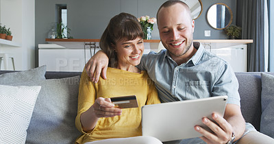 Buy stock photo Cropped shot of an affectionate young couple using a digital tablet and a credit card while shopping online in their living room at home