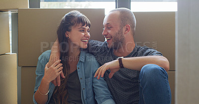 Buy stock photo Cropped shot of an affectionate young couple laughing together while sitting together in their new home on moving day