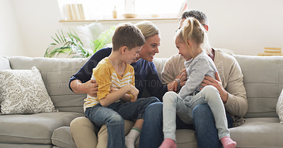 Buy stock photo Shot of a happy family tickling each other while sitting on the couch at home