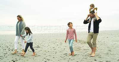 Buy stock photo Shot of a happy family walking along the beach