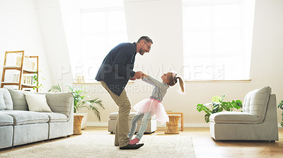 Buy stock photo Shot of a father dancing with his little daughter at home