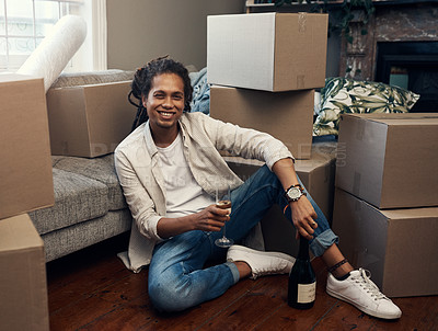Buy stock photo Shot of a handsome young man having champagne to celebrate moving into his new house