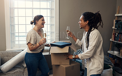 Buy stock photo Shot of a happy young couple having champagne to celebrate their new home