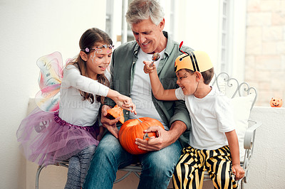 Buy stock photo Shot of two adorable young siblings carving out pumpkins for Halloween with their grandfather at home