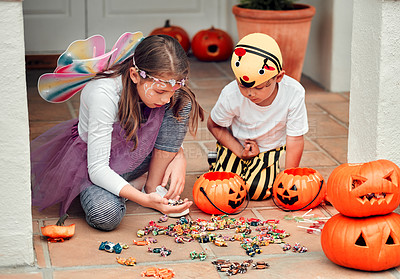 Buy stock photo Shot of two adorable young siblings looking at their Halloween candy at home