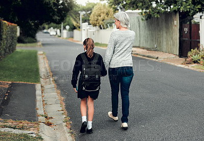 Buy stock photo Full length shot of a young school girl walking with her grandmother to school in the streets in their neighborhood