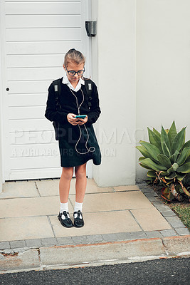 Buy stock photo Full length shot of a young schoolgirl listening to music and using her cellphone while standing outside her house