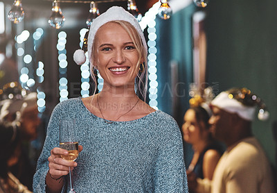 Buy stock photo Portrait of a cheerful young woman wearing a festive hat and holding a glass of wine at home during christmas time