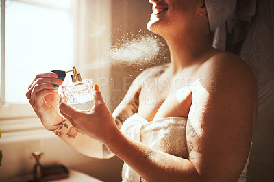 Buy stock photo Cropped shot of a young woman spraying perfume during her morning beauty routine