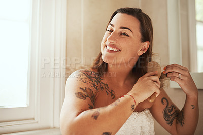 Buy stock photo Shot of an attractive young woman brushing her hair during her morning beauty routine at home