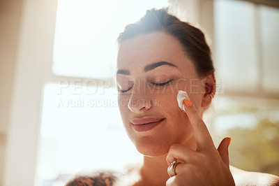 Buy stock photo Shot of an attractive young woman applying moisturiser during her morning beauty routine