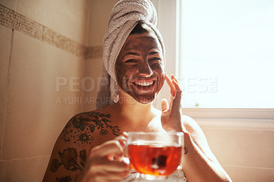 Buy stock photo Shot of a young woman having tea while giving herself a facial at home