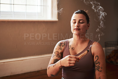 Buy stock photo Shot of a young woman burning a palo santo stick at home