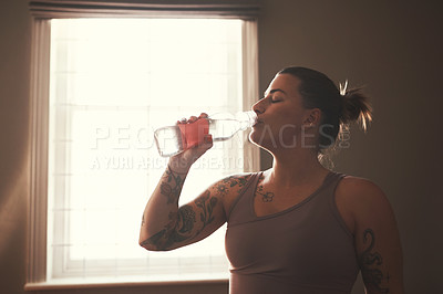 Buy stock photo Shot of a young woman drinking water after her workout at home