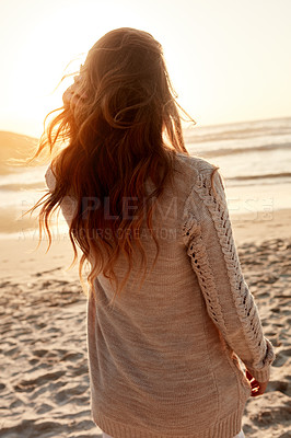 Buy stock photo Rearview shot of a young woman spending some time at the beach