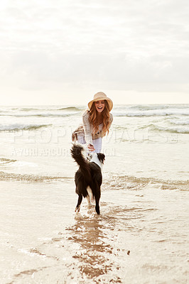 Buy stock photo Shot of a young woman spending some time with her dog at the beach
