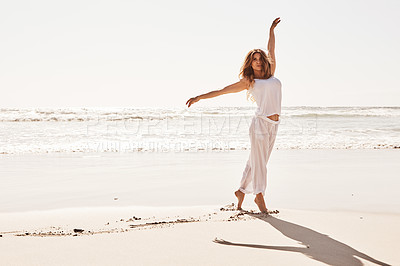 Buy stock photo Shot of a young woman standing with her arms outstretched at the beach
