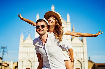 Buy stock photo Shot of a happy young couple enjoying a piggyback in the city of Florence