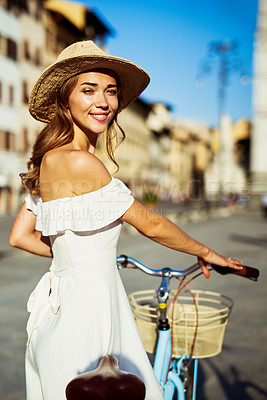 Buy stock photo Shot of a happy young woman spending the day with her bicycle in the city of Florence