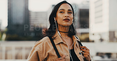 Buy stock photo Shot of a young woman wearing earphones while out in the city