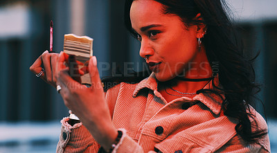 Buy stock photo Cropped shot of a young woman applying lipstick while looking into a pocket mirror
