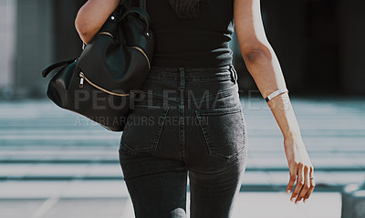 Buy stock photo Cropped shot of an unrecognizable woman carrying a backpack while walking through the city