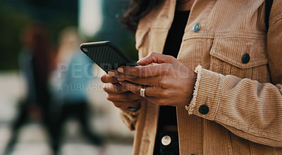 Buy stock photo Cropped shot of an unrecognizable woman using her cellphone while out in the city