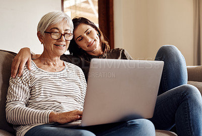 Buy stock photo Shot of a young woman using a laptop with her elderly mother on the sofa at home