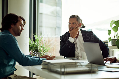 Buy stock photo Shot of a mature businessman having a discussion with a colleague in an office