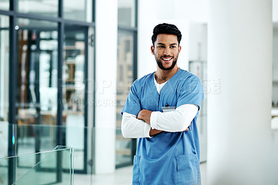 Buy stock photo Shot of a young medical practitioner standing with his arms crossed in a hospital