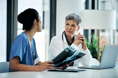 Buy stock photo Shot of two medical practitioners having a discussion in a hospital boardroom