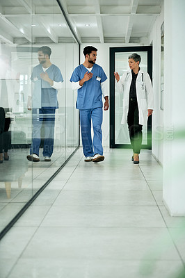 Buy stock photo Shot of two medical practitioners walking through a corridor in a hospital