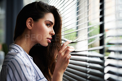 Buy stock photo Cropped shot of an attractive young woman looking through her window while standing indoors at home